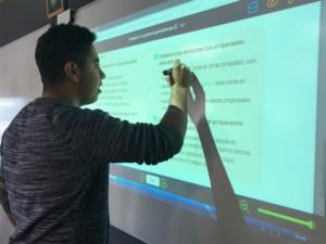 Alumne utilitzant una pissarra digital.